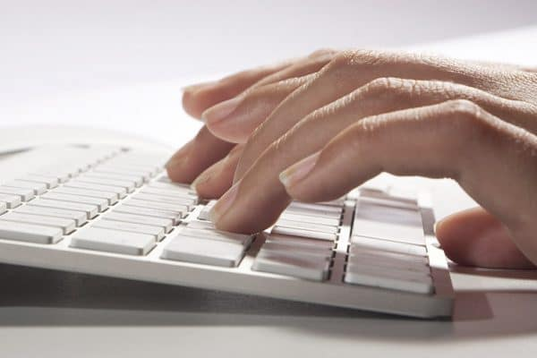 Persona tecleando en Apple Keyboard